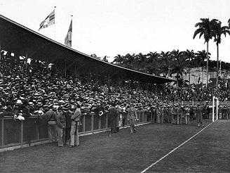 A arquibancada repleta, protegida por policiais, atrás do gol da atual Rua Pinheiro Machado. No alto da foto observamos a bandeira da extinta Confederação Brasileira de Desportos (CBD).